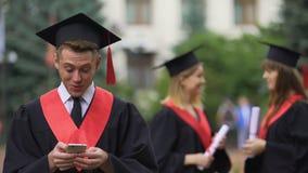 Mannesgraduierte Lesegute Nachrichten auf Smartphone vor Zeremonie, Erstaunen stock video