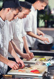 Mannesköche, die Sushi zubereiten Lizenzfreie Stockfotos