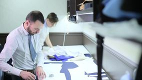 Mannesschneider, die mit Skizzen arbeiten stock footage