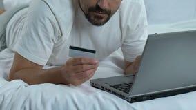 Mannetje in bed die kaartaantal op laptop toepassing, online bankwezen, het winkelen ingaan stock footage