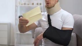 Mannetje in cervicale kraag en wapenslinger het openen envelop met rekening die één hand gebruiken stock video