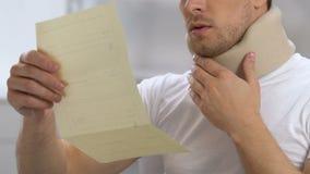 Mannetje in cervicale kraag het openen envelop met behandelingsrekening, verzekeringsprobleem stock videobeelden
