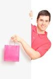 Mannetje dat een zak houdt en zich achter paneel bevindt Stock Afbeeldingen