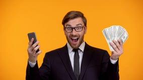 Mannetje dat smartphone bekijkt en onmiddellijk de achterinschrijving van het geldcontante geld ontvangt royalty-vrije stock foto's