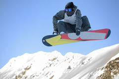 Mannetje dat snowboarder met snowboard springt Stock Foto