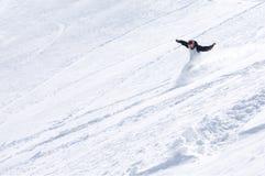 Mannetje dat snowboarder onderaan de berg glijdt Stock Fotografie