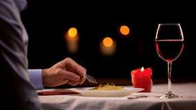 Mannetje dat van gastronomisch diner in restaurant geniet, deegwaren eet en wijn drinkt stock afbeelding