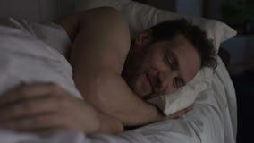 Mannetje die in bed alvorens in slaap, prettige gedachten positieve ervaring te vallen glimlachen stock footage