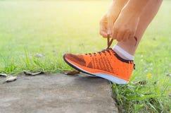 Mannetje die en sportenschoenen voor jogging en oefening voorbereiden dragen stock foto's