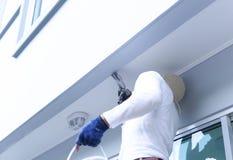 Mannetje die in handschoenen pijnborstel het schilderen de bouw houden royalty-vrije stock afbeeldingen