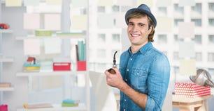 Mannetje die hipster terwijl het houden van rokende pijp glimlachen Stock Fotografie
