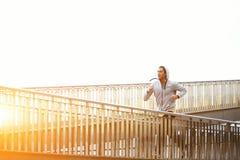 Mannetje die jogger terwijl het luisteren aan muziek met hoofdtelefoons uitoefenen stock foto's