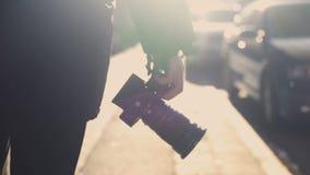 Mannetje die op camera van de straatholding, lopen die schietend plaats, hobby de zoeken stock videobeelden