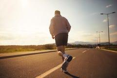 Mannetje die op de weg lopen Van de rug Stock Afbeeldingen