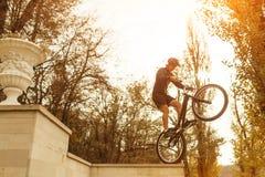 Mannetje die truc op fiets uitvoeren Stock Foto's
