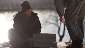 Mannetje die voor geld met kartonteken bedelen stock footage