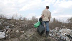 Mannetje die zich op de heuvel bij de plaats van de huisvuilstortplaats bevinden stock footage