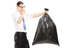 Mannetje die zijn neus sluiten en een stinky vuilniszak dragen stock afbeelding