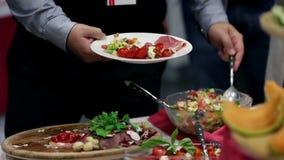 Mannetje die zijn plaat vullen met wat salades en vlees stock footage