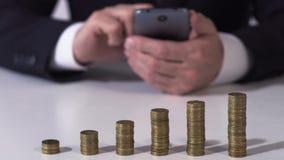 Mannetje in klassiek kostuum het berekenen inkomen op cellphone, financiën en investering stock footage