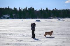 Mens die met hond binoculair bekijken stock fotografie