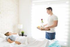 Mannetje met Ontbijt Tray Looking At Female Sleeping in Bed stock afbeelding