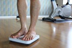 Mannetje op de gewichtsschaal voor controlegewicht, Dieetconcept royalty-vrije stock foto