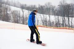 Mannetje snowboarder op helling bij de wintertoevlucht stock afbeeldingen