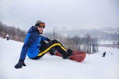 Mannetje snowboarder op helling bij de wintertoevlucht stock foto's