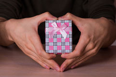 Mannetje twee dient vorm die van hart in roze geruite giftdoos houden Royalty-vrije Stock Foto's