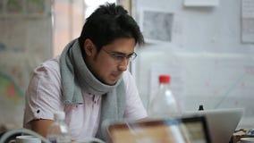 Mannetje van Aziatische verschijningscartograaf in glazen en sjaal die aan laptop werken stock footage