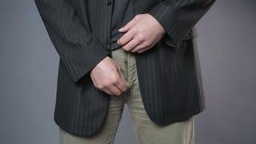 Mannetje in zwart jasje die zijn broekritssluiting, verlegenheid, man gezondheid trekken stock video