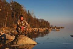 Mannfänge fischen Stellung auf Steinen im Wasser lizenzfreies stockbild