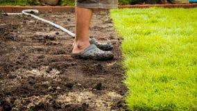 Mannfüße herüber mit Gras zu bedecken vom Boden Lizenzfreie Stockfotos