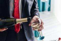 Mannfüllung verzierte Glas mit Champagner Lizenzfreies Stockbild