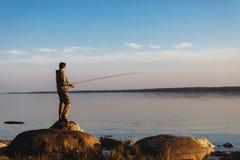 Mannf?nge fischen Stellung auf Steinen im Wasser lizenzfreie stockfotos