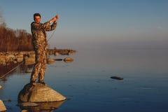 Mannf?nge fischen Stellung auf Steinen im Wasser stockfoto