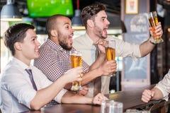 Mannfans, die im Fernsehen Fußball und Getränkbier schreien und aufpassen T Stockbilder
