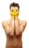 Mannfell sein Gesicht unter Lächelnschablone Stockfoto