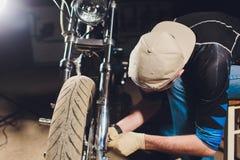 Mannfestlegungsfahrrad ?berzeugter junger Mann, der Motorrad nahe seiner Garage repariert lizenzfreie stockbilder