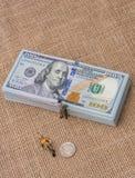 Mannfigürchen neben dem Bündel von US-Dollar Banknote Lizenzfreies Stockbild