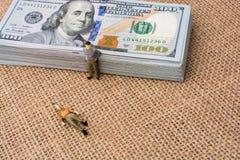 Mannfigürchen neben dem Bündel von US-Dollar Banknote Stockfotos