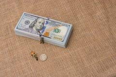 Mannfigürchen neben dem Bündel von US-Dollar Banknote Lizenzfreie Stockbilder