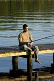 Mannfischen auf einem Dock Stockbild