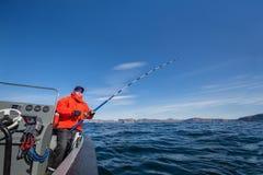 Mannfischen von einem Boot mit dem Spinnen Rote Jacke trägt glasse zur Schau Lizenzfreies Stockbild