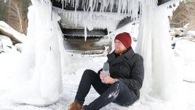 Mannfischer, der mit einer Thermosflasche auf dem See und dem trinkenden Tee sitzt stockbilder