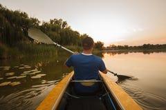 Mannflöße auf dem Kajak Kajakmannsonnenuntergang-Wassersport lizenzfreies stockfoto