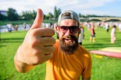 Mannfröhliches gesicht zeigt sich Daumen Mann bärtig vor Mengenflußuferhintergrund Sommerfestival der Buchkarte jetzt lizenzfreie stockfotos