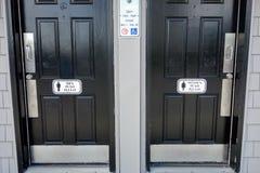 Mannfrauen, die schwarze Badezimmertüren mit Männern unterzeichnen drücken bitte, auf Tür Stockfotografie