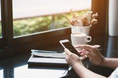 Manngebrauch Smartphones in den Cafés und in der weichen Beleuchtung Stockbild